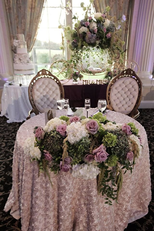 This sweetheart table is perfect for any spring wedding, draped in a champagne linen with cascading flowers in purple, green and white #springwedding #springweddingideas