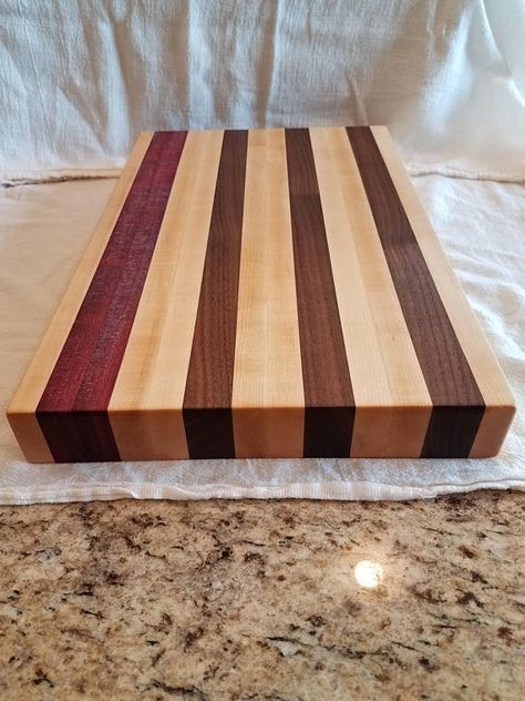 This cutting board is made of purple heart, maple and walnut wood. Great for wedding, Christmas, birthday gift or any occasion. Food safe mineral oil and butcher block wood conditioner was used to protect the wood. Dimensions: 10W x 15L x 1 1/2 thickness (Sizes may vary slightly)