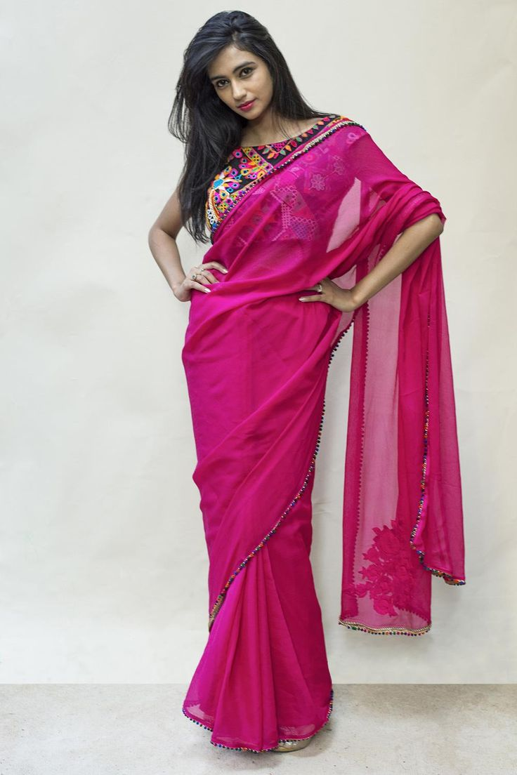 A fuchsia pink drape edged with subtly playful multi coloured pom pom's. The pink gold appliqué of roses on the pallu adds the finishing touch to this gape-worthy saree. Pair with a blouse in cool warm color like deep turquoise or purplish gray to add some sophistication. A floral blouse for the day, a sheer gold blouse for the night. A solid coloured saree is truly your blank canvas. #houseofblouse #saree #blouse #indianwear #india #fashion #bollywood #pink #chiffon
