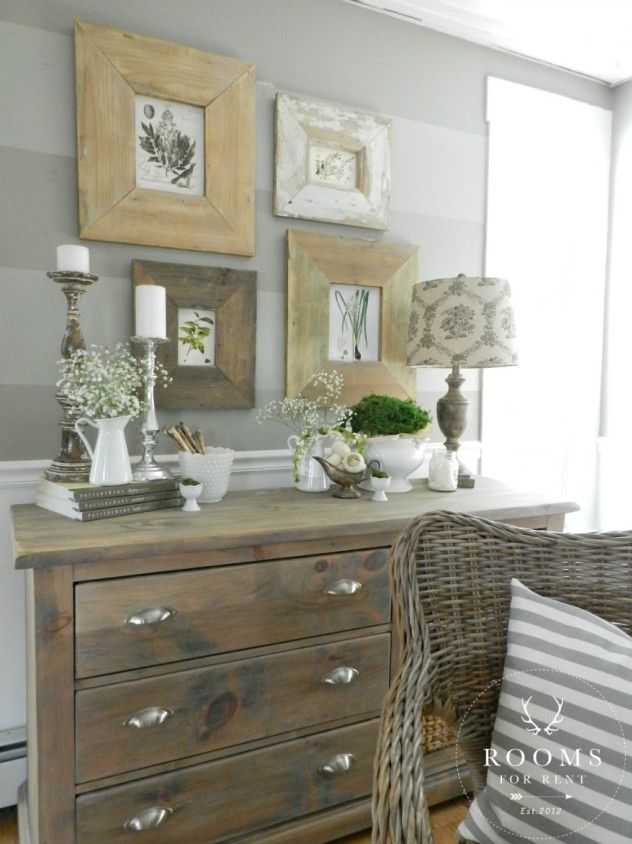 Love the wall prints & the wood tone mixed w silver and grey striped pillow w rattan chair