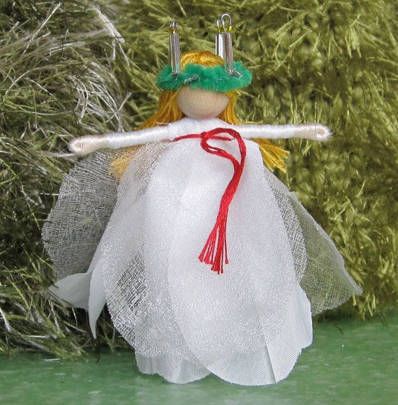 Santa Lucia Christmas fairy - Saint Lucia - Saint Lucy - miniature doll-by TracysGardenFairies on Etsy This little flower fairy is Santa Lucia. Her dress is a white rose, she has the traditional red waist band and her crown of candles. Her feast day is celebrated on Dec. 13. Her crown is made of pipecleaner, wire and glass beads. Please use care when using this doll.