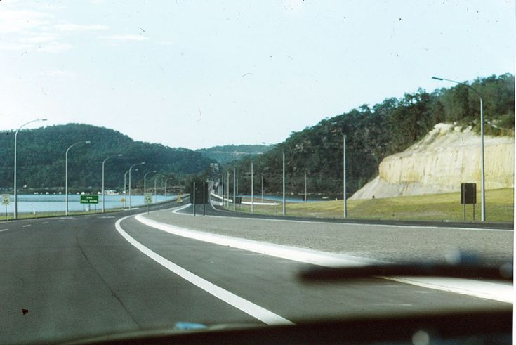 Looking south from the toll booths (the driver would have just paid the toll before this photo was taken) towards the merge with Pacific Highway and the Hawkesbury River bridge.  Source: Kevin Noble, January 1966.