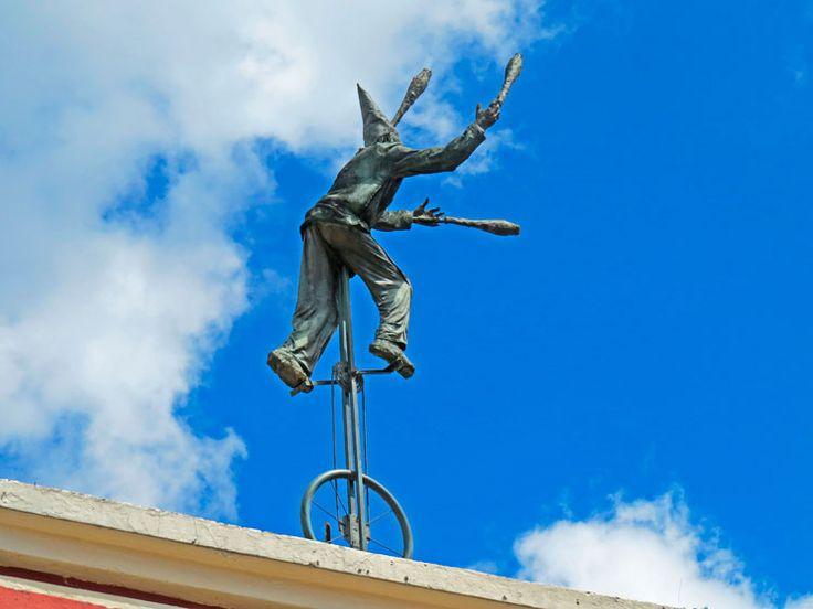 6. En la parte superior del muro hay una escultura de un malabarista subido en un monociclo y jugando con clavas o pines de bolos