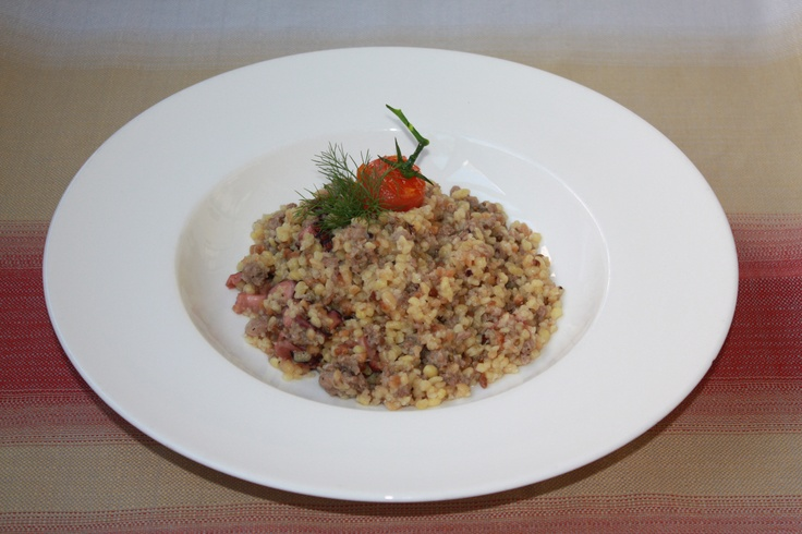 Traditional fregola pasta with stewed octopus and sausage chunks with local red wine.