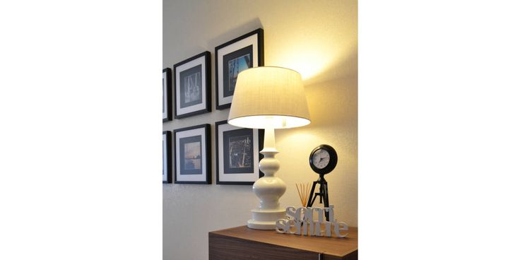 Simple, classic, white lamp on wooden side table. Lighting by T2 Arquitectura & Interiores