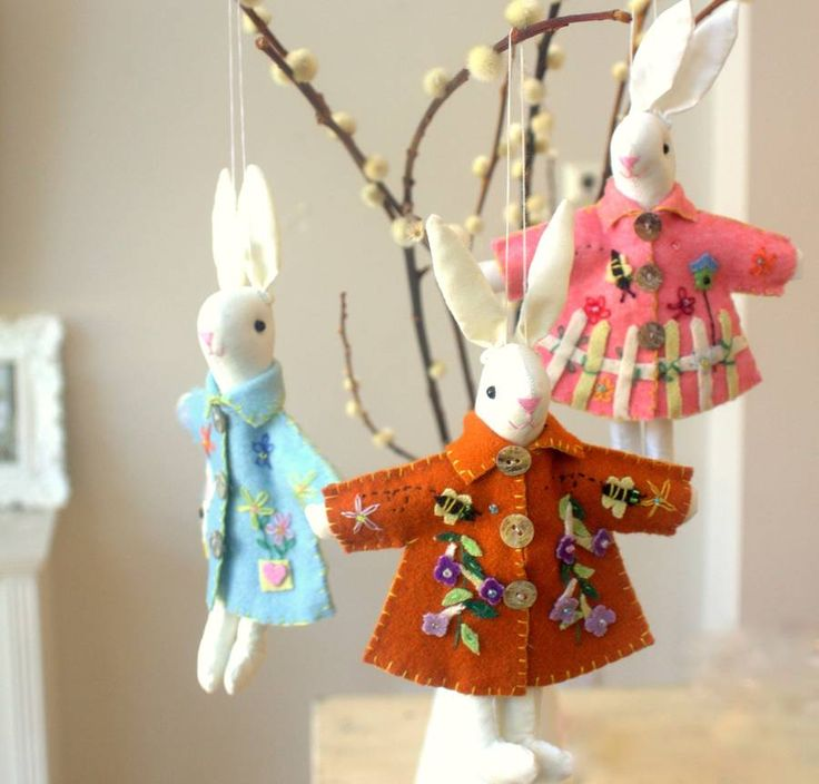 Cream bunny rabbits with embroidered Easter coats .These adorable cream hanging bunny decorations are delicately embroidered with miniature flowers and bumble bees. Each rabbit is wearing a felt coat, available in either orange, pale blue or pink. The jackets are finished with three shiny shell buttons. They can be hung from a Easter tree or branch and will be loved by all ages.Cotton , plastic buttonsH 8cm