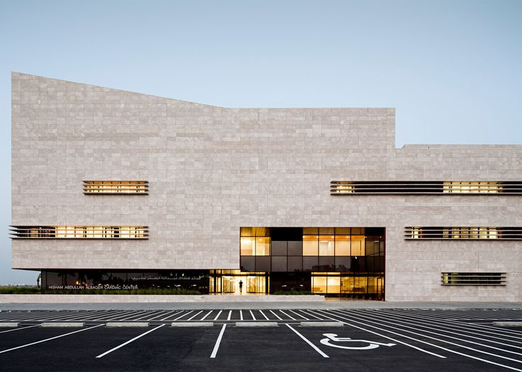 With stone-clad walls and a deep red atrium, this medical centre in Kuwait was designed by AGi architects to look more like a cultural building than a health facility