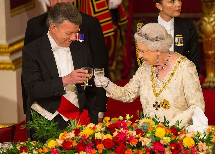 SHE HOSTS AN AVERAGE OF 50,000 PEOPLE EVERY YEAR AT RECEPTIONS, BANQUETS, LUNCHES, DINNERS, AND GARDEN PARTIES AT BUCKINGHAM PALACE. Seen here toasting Colombia's President Juan Manuel Santos. TownandCountrymag.com