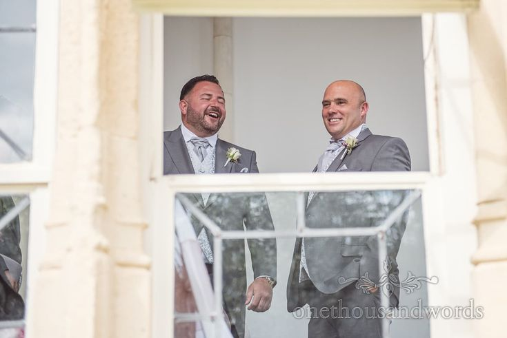Groom and best men laughing through window at Highcliffe Castle Wedding venue. Photography by one thousand words wedding photographers