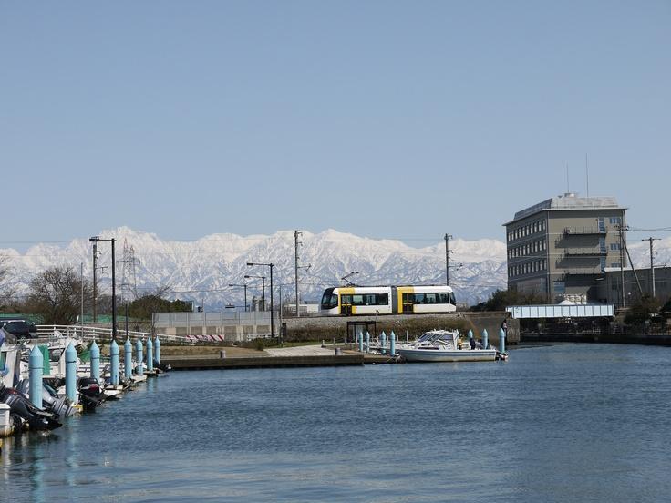 PORTRAM (Toyama Light Rail) viewing peaks of Tateyama from Iwase canal.