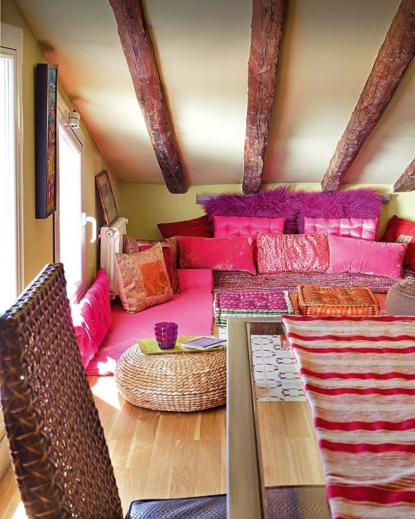 This is a bohemian styled room. The different shades of pink, fushia and purple textured pillows together with the rustic weaved furniture put around subtly brings the room a somehow down to earth welcoming feel.