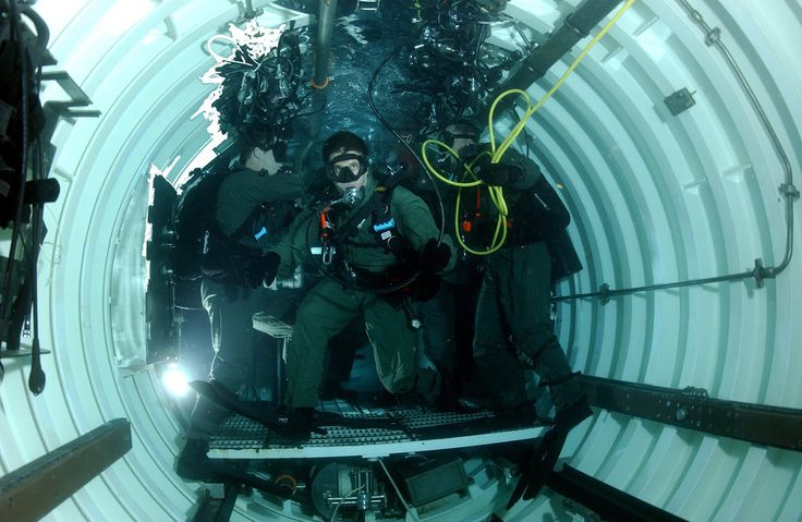 050505-N-3093M-009 Members of SEAL Delivery Vehicle Team Two hang out inside a flooded dry deck shelter mounted on the back of the USS Philidelphia. The dry deck shelter is used to house and luanch the team's SEAL delivery vehicles (SDV) while the sub is underway. The SDVs transport Navy SEALs from their submerged host submarine to targets while remaining underwater and undetected. Official U.S. Navy Photograph By:Chief Photographer's Mate ( Diver) Andrew McKaskle, Fleet Combat Camera…