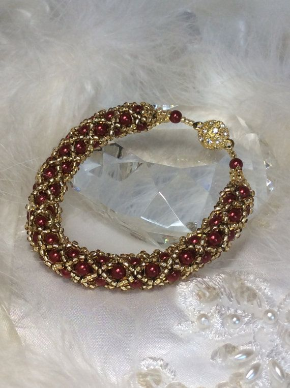 This handmade bracelet features a tubular shape and is made up of 4mm round red glass beads accented with gold seed beads. This handwoven piece is held together with black wildfire thread and closed with a gold magnetic clasp The bracelets actual length is 19 cm (7.5 inches) but
