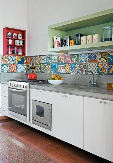 cucina bianca rigorosa, piastrelle colorate e pensili a giorno in tinta.
