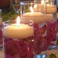 Purple flowers immersed under a romantic floating candle.