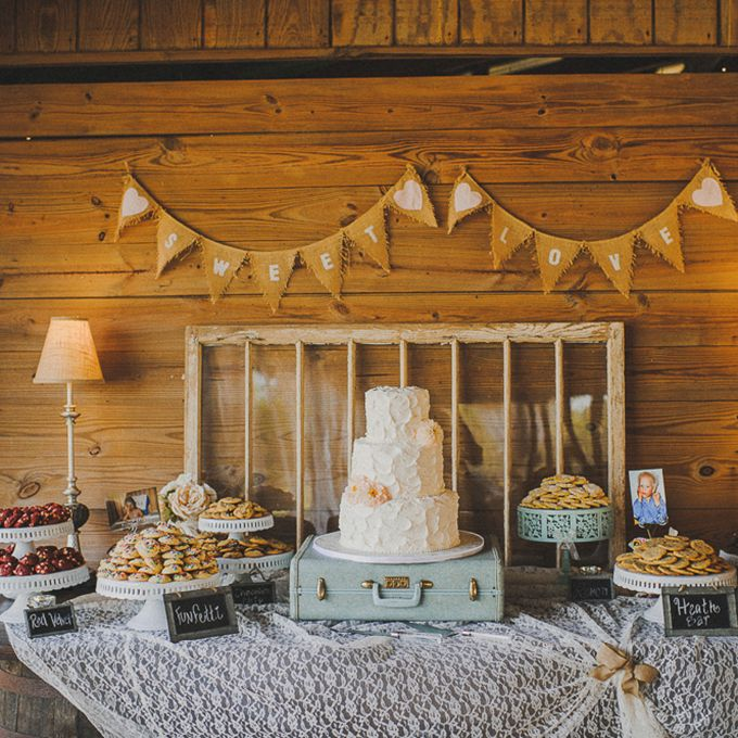 Brides.com: . Vintage cookie dessert bar with a suitcase cake stand, flag banners, and a distressed windowpane backdrop.