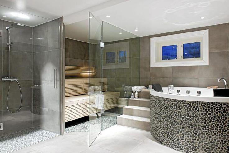 Baderommet er romslig og lekkert, og minner mer om et spa med sitt store boblebad og sauna. Her er det brukt flere ulike typer fliser, både store og små mosaikkfliser. Fargetonene er duse jordtoner.