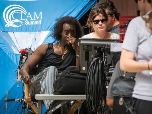 """Cincinnati-shot Miles Davis film set for fall premiere. Photo: Star-director Don Cheadle looks at a monitor between shots on """"Miles Ahead,"""" his movie about jazz great Miles Davis, on Seventh Street near Elm Street on July 7, the first day of filming. The Enquirer/Madison Schmidt"""