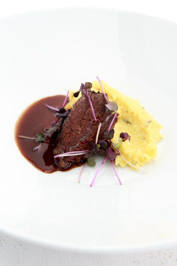 Leckere, langsam geschmorte Ochsenbäckchen mit einer kräftigen Rotweinsauce, dazu cremige Polenta, mit Orange aromatisiert.