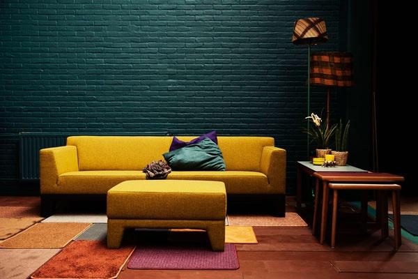 Sofá Plot en color mostaza que contrasta con el muro en tono verde azulado. Ambos colores mantienen la misma intensidad de color, y son colores lisos a pesar de la textura del muro que ayuda a realzar el color.