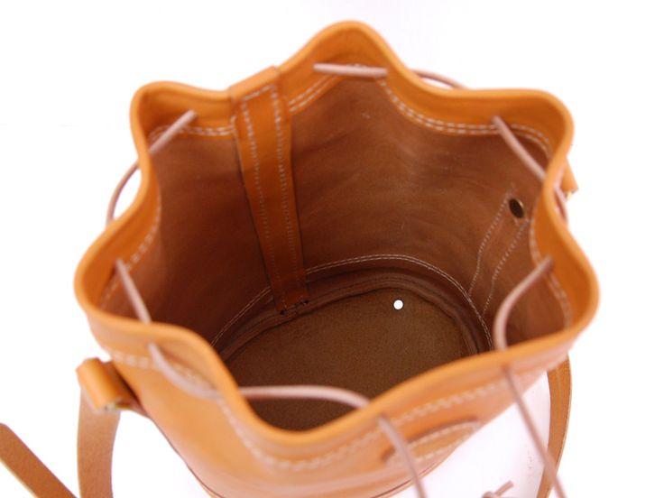 本体口を革紐でしぼって使う、「巾着」をショルダーバッグにしました。楕円形のマチでお弁当やカメラなど立体のものを収納することもできます。2サイズ展開で、用途と雰囲気に合わせてお選びいただけます。