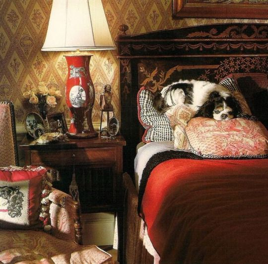 Red accessories- lamp, pillows blanket/spread against neutral walls