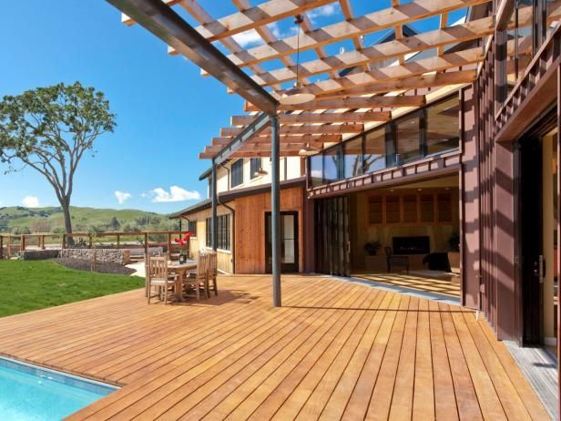 An outdoor pool becomes secondary to the beautiful pergolas and decking that surround it in this example of Garapa , an exotic hardwood that ranges in color from light yellow to golden hues and is resistant to rot, decay and insect damage.