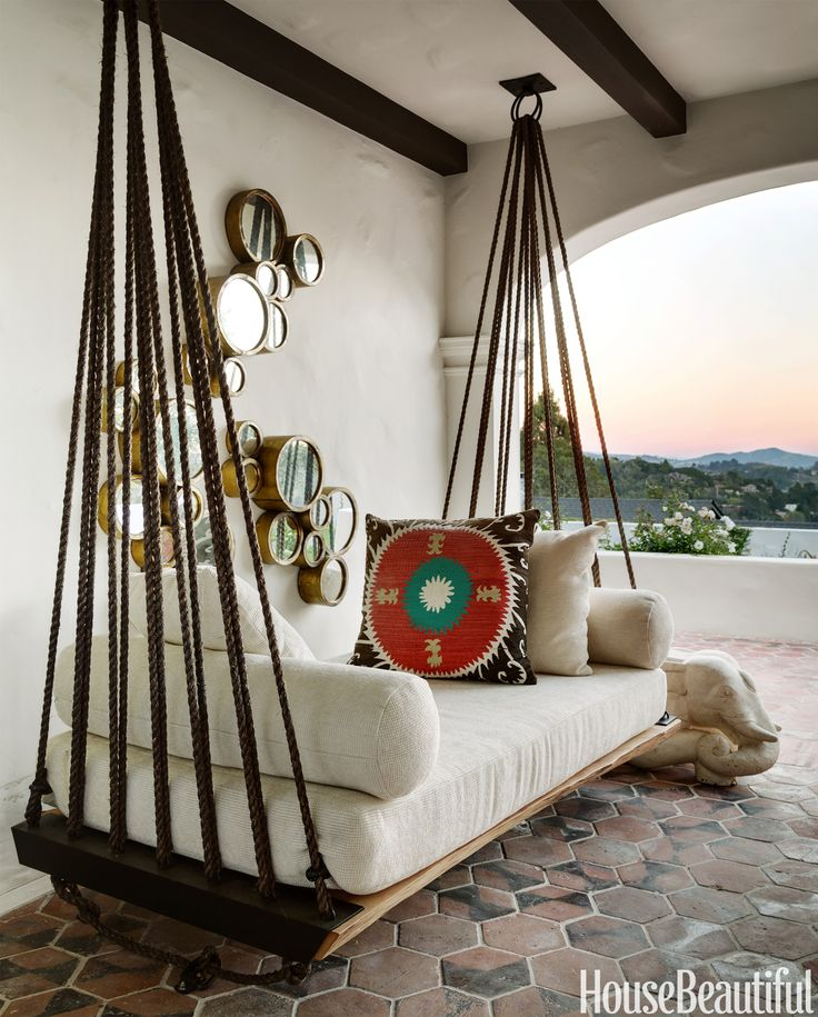 Responding to her clients' request for a swing where they could enjoy the view of Mount Tamalpais and the hills of San Francisco in this Spanish Colonial home, designer Erin Martin used rope, metal rings, and wood to improvise this hammock/divan on the loggia.   - HouseBeautiful.com