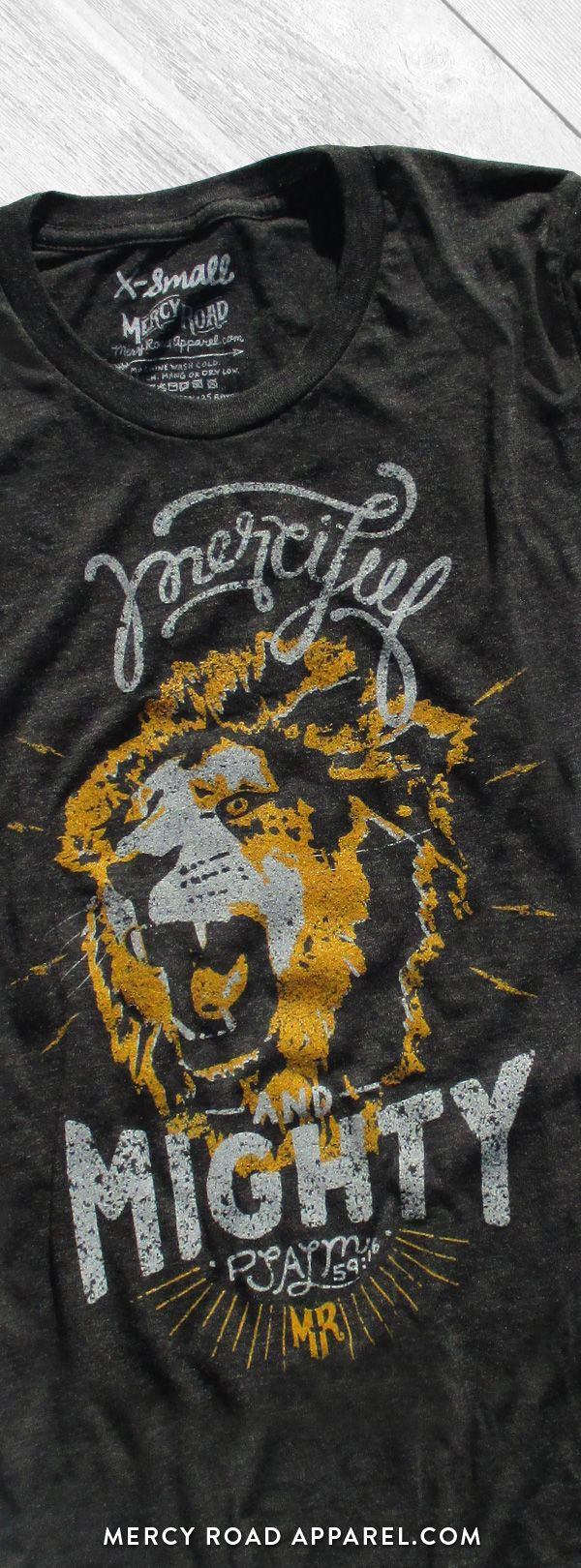 "Christian T-Shirt with Jesus as the lion of Judah, a roaring lion and Psalm 59:16 ""Merciful and Mighty."" This scripture shirt is handcrafted and screenprinted on a gloriously comfy charcoal black triblend tee. Quality Christian clothing for women and men. FREE SHIPPING USA. Shop >> MercyRoadApparel.com"