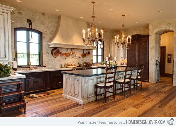 15 Stunning Mediterranean Kitchen Designs - Wye River Estate | Image: Pyramid Builders | We think everything about this room is amazing. The rustic stone walls and limestone vent hood contrasts perfectly with the elegant chandeliers and detailed cabinetry.