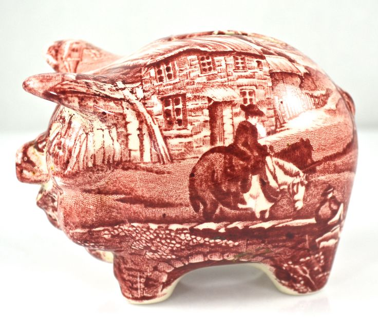 OINK OINK Here is a darling little piggy bank, shaped like a plump pig. It has a red transfer print with a man riding his horse across a bridge into a picturesque English Village. JAMES KENT FOLEY STA