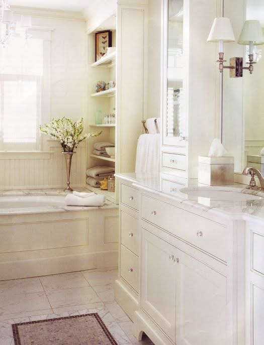 Elegant bath.  Built-in shelving + sconces + marble