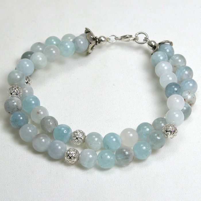 "Handmade gemstone aquamarine bracelet features a 2 strands of semi-precious, round aquamarine gemstones, sterling silver accent beads, stretch band, and lobster claw clasp. 8"" in length. Add a necklac"