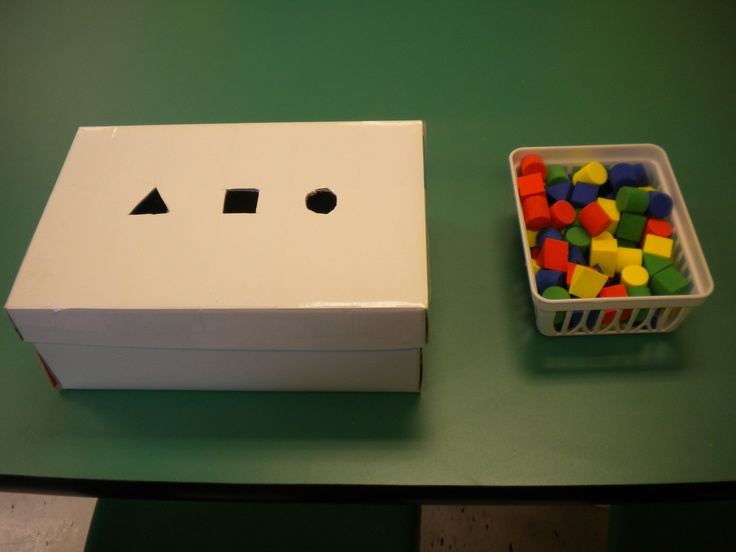 Sort by shape.  Take an old shoe box, cover with paper, cut holes of shapes slightly larger.  I inserted dividers inside the box so I could check work easily. The shapes were purchased at the dollar spot in Target.