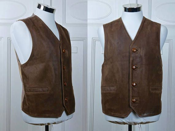 Veste en cuir marron American vintage présente des hommes a un look bien usé, mais est toujours en excellent état. Le cuir est un daim velouté, et le devant se ferme par quatre boutons d'ameublement marron très grand. Le gilet en cuir rocker a deux poches à fente à l'avant, est
