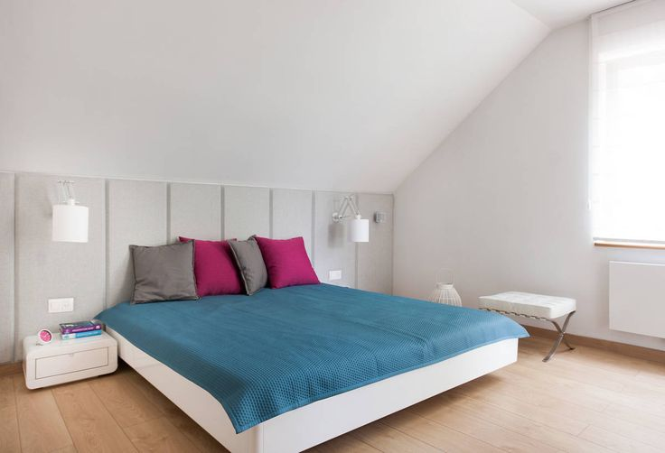 Bedroom with Blue Quilt and Colorful Cushions near White Drawers
