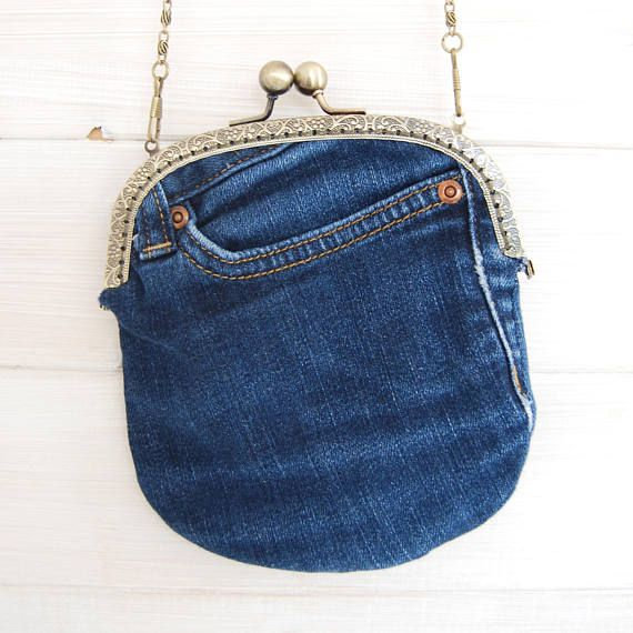 Denim clutch bag, made from up cycled jeans. With aged brass frame and floral interior. Size of bag approx 16cm wide x 20cm high Chain length 125cm