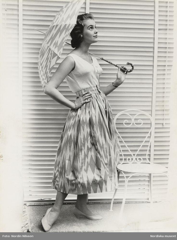 """Tonårsmode. Modell i vitt linne, kjol och paraply i Gråstens-mönster, vid en stol. Tyget heter """"Kalas"""" och designades av Viola Gråsten för NK:s textilkammare 1955. Fotograf: Nordin Nilsson, 1955"""