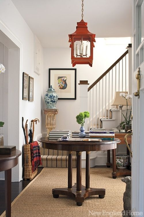 Love all the eclectically preppy touches (red pagoda lantern, blue and white china, rattan walking stick stand with tartan blanket, etc) against clean white walls.