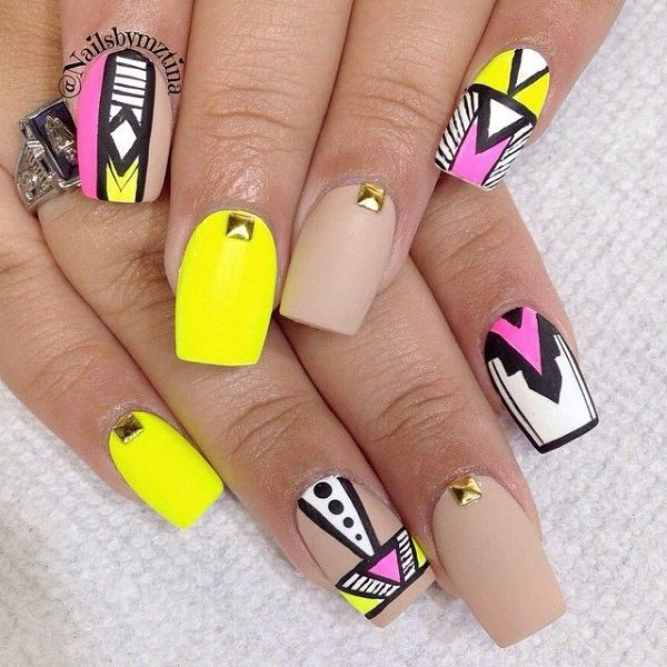 Wonderful looking tribal inspired yellow nail art design. A combination of matte and playful tribal designs. The nails are painted with nude and yellow matte colors plus colorful polishes for the tribal designs. To add to the effect gold embellishments are added on top.