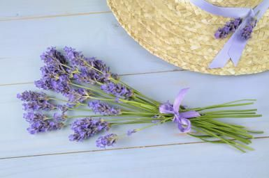Lavender bunch and straw hat on wooden table. - Cora Niele/Photolibrary/Getty Images