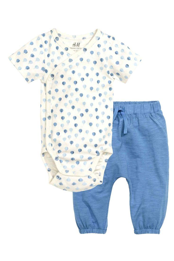 Body croisé et pantalon: CONSCIOUS. Ensemble en jersey souple de coton bio. Body croisé avec motif imprimé et manches courtes. Fermeture pressionnée sur un côté et à l'entrejambe. Pantalon avec élastique et lien de serrage décoratif à la taille. Élastique en bas de jambe.
