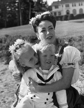Joan Crawford hugging her two adopted children, Christina and Christopher, while sitting on beach, 1945.