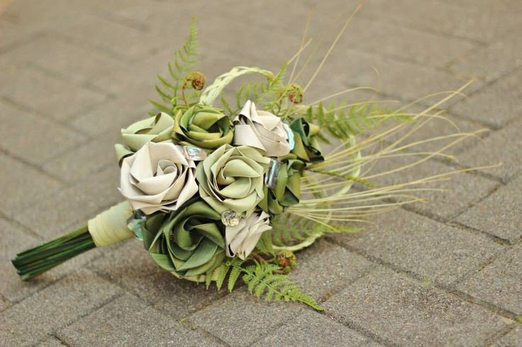 Cascading bouquet in sage, pale green and ivory with fern, koru and paua.    www.flaxation.co.nz