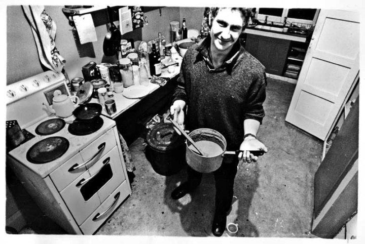 """Peter in his kitchen in 1984. Site caption: The Gut shows off Stu's brew: """"Steve inspired"""" San Pedro cactus wine."""