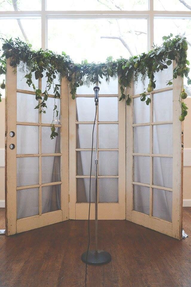 Easy and classy wedding ceremony backdrop. Old doors with cheap grey fabric tacked behind and a beautiful greenery garland