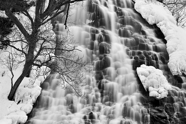 $150. Black and white close-up waterfall view of Oshinkoshin Falls in winter with ice and cascades near Shiretoko National Park on the island of Hokkaido in Japan.