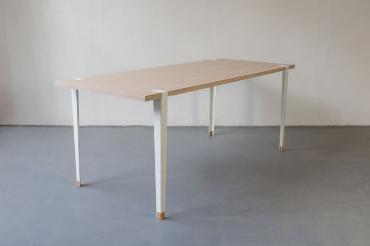 A folded sheet of steel creates the legs for this minimalistic table. The legs simply slide onto the wooden table top. There are no connecting parts such as screws or nails required. The table has leather feet to protect the floor. The result is a very easily assembled table with an elegant look.