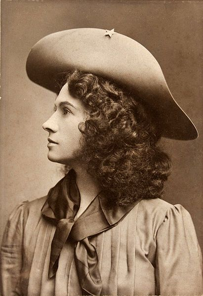 """Annie Oakley, """"Little Sure Shot"""", American sharpshooter and exhibition shooter. She became the first American female superstar in Buffalo Bill's Wild West show in 1885. Her most famous trick was to repeatedly split a playing card, edge-on, and put several more holes in it before it could touch the ground, while using a .22 caliber rifle, at 90 feet."""
