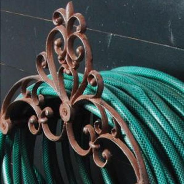 Sure, you could just coil your hose and hide it under a bush, but this Victorian inspired cast iron holder elevates the common hose to an uncommon garden accent. No kinks or muddy mess to contend with...